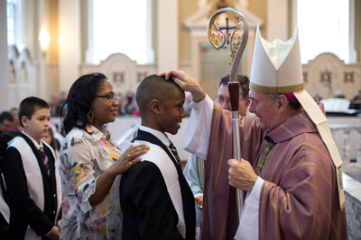 Young man being Confirmed by the Bishop